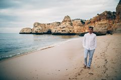 Young happy man walking in j a white shirt on the beach and the sea at sunset royalty free stock photos