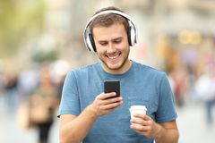 Happy man walking listening to music. Front view of a happy man walking listening to music wearing headphones and holding a take away drink on the street Stock Images