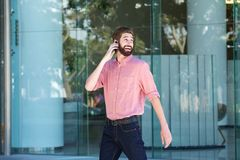 Happy man walking outside in city talking on cellphone. Portrait of happy man walking outside in city talking on cellphone Stock Images