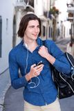 Happy man walking outside with phone and headphones. Portrait of happy man walking oute with phone and headphones Stock Images