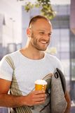 Happy man walking on street holding coffee Royalty Free Stock Photography