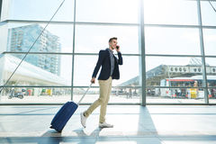 Happy man walking with suitcase and phone in airport Stock Images