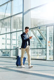 Happy man walking with suitcase and phone in terminal. Full length portrait of happy man walking with suitcase and phone in terminal Stock Image