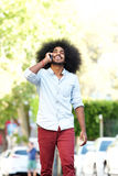 Happy man walking and talking outside with mobile phone Stock Photography