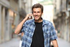 Happy man walking talking on phone in a old town street. Front view of a happy man walking talking on smart phone in an old town street stock photo