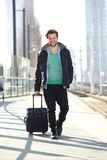 Happy man walking on train station platform with bag Stock Photos