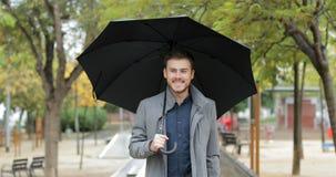 Happy man walking under the rain in winter. Front view portrait of a happy man walking holding an umbrella under the rain in winter in a park stock video