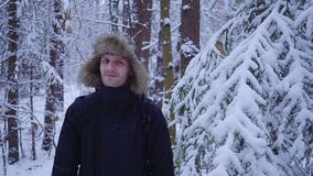Happy man walks in the cold winter forest covered with snow. Hd stock video footage