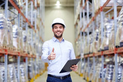 Happy man at warehouse showing thumbs up gesture Stock Photography