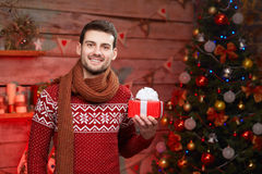 Happy man in warm clothes with gift box at home Stock Images