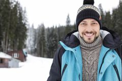 Happy man in warm clothes outdoors, space for text. Winter vacation stock photography