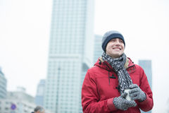 Happy man in warm clothing holding disposable cup outdoors Stock Photo