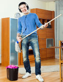 Happy man washing parquet floor with mop in living room at home Stock Image
