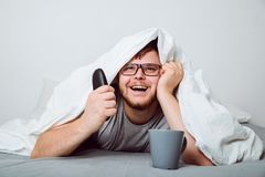 Happy man watch TV under blanket. With cup of coffee Stock Photos