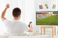 Happy man watching football or soccer game on tv Royalty Free Stock Images