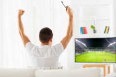 Happy man watching football or soccer game on tv. Leisure, technology, mass media and people concept - happy man watching football or soccer game on tv and Royalty Free Stock Photography