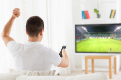Happy man watching football or soccer game on tv. Leisure, technology, mass media and people concept - happy man watching football or soccer game on tv and Stock Images