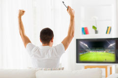 Happy man watching football on tv at home. Leisure, technology, media, sport and people concept - man watching football game on tv and supporting team at home Stock Images