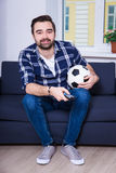 Happy man watching football on tv at home. Happy young man watching football on tv at home Royalty Free Stock Photo