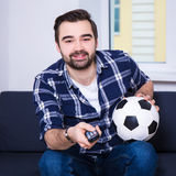 Happy man watching soccer on tv. Happy young man watching soccer on tv Royalty Free Stock Photography