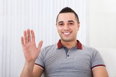 Happy man waving at home Stock Images