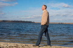 Happy man, wearing casually, walking along the beach, in magic a Stock Photos