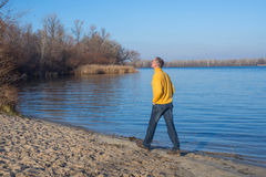 Happy man, wearing casually, walking along the beach, thinking a Royalty Free Stock Photo