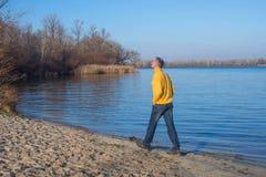 Happy man, wearing casually, walking along the beach, thinking a Royalty Free Stock Photo