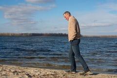Happy man, wearing casually, walking along the coast , thinking Royalty Free Stock Photos