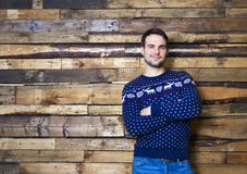 Happy man wearing Christmas sweater against wall background. Happy man wearing Christmas sweater against wooden wall background royalty free stock photos