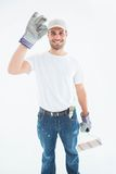 Happy man wearing gloves while holding paint roller Royalty Free Stock Image