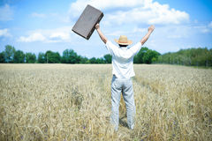 Happy man wearing hat with suitcase rising hands Stock Photos
