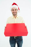 Happy man wearing Santa hat while holding red gift. Portrait of happy man wearing Santa hat while holding red gift on white background Stock Photos