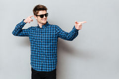 Happy man wearing sunglasses pointing. Image of young happy man wearing sunglasses standing over grey wall and looking aside while pointing Stock Photography