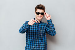 Happy man wearing sunglasses pointing stock photography