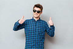 Happy man wearing sunglasses showing thumbs up. Photo of young happy man wearing sunglasses standing over grey wall and looking at camera. Showing thumbs up royalty free stock photos