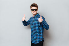 Happy man wearing sunglasses standing over grey wall. Photo of young happy man wearing sunglasses standing over grey wall and looking at camera. Showing thumbs stock photos