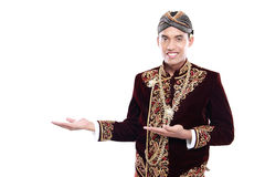 Happy of man wearing traditional of java presenting blank area Royalty Free Stock Image