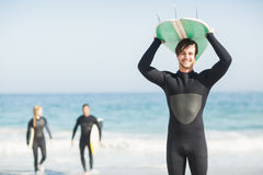 Happy man in wetsuit carrying surfboard over head Royalty Free Stock Photography
