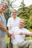 Happy man in a wheelchair with his nurse and wife Stock Photo