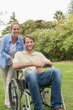 Happy man in wheelchair with partner Stock Images