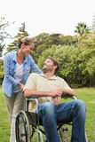Happy man in wheelchair talking with partner Stock Images