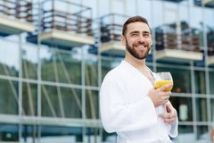 Restful man. Happy man in white bathrobe holding glass of orange juice while spending vacation in luxurious hotel of spa resort Royalty Free Stock Images