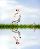 Happy man in white clothes is jumping. Over the grass near the lake Stock Image