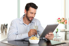Happy man with wine and tablet at the bar stock photography