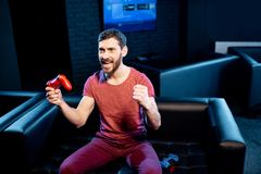 Happy man playing video games with gaming console in the club royalty free stock photography