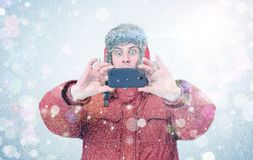 Happy man in winter clothes with smartphone. Frost, sun, snow, flares Stock Image