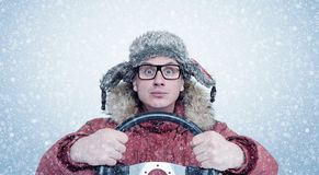 Happy man in winter clothes with a steering wheel, snow blizzard. Concept car driver.  Royalty Free Stock Photography