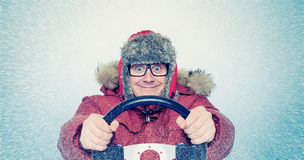 Happy Man in winter clothes with a steering wheel, snow blizzard. Concept car driver