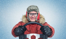 Happy Man in winter clothes with a steering wheel, snow blizzard. Concept car driver. Stock Photo
